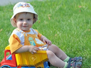 5290885-a-smiling-baby-with-a-pacifier-is-sitting-in-the-toy-truck-on-the-grass-Stock-Photo